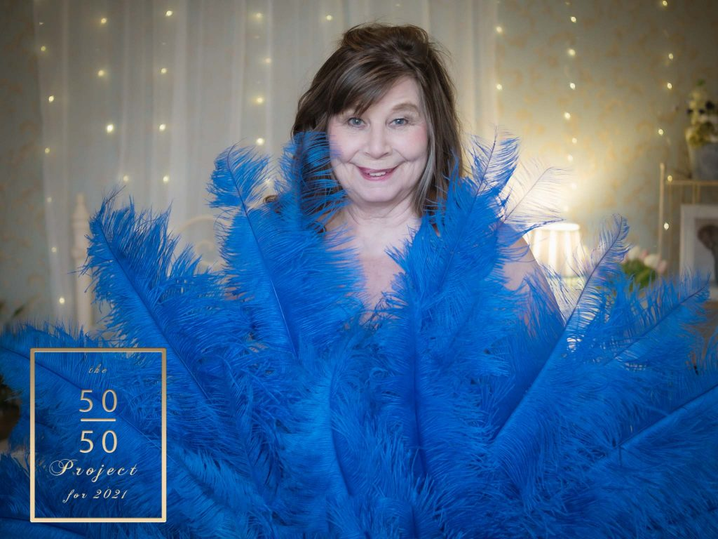 mature woman with burlesque feathers for her 50 over 50 project shoot