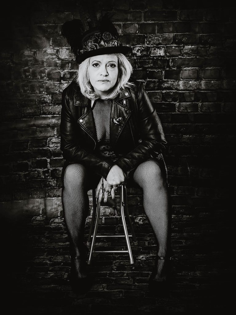 woman in leather jacket against a brick wall posing for the 50 over 50 project boudoir shoot