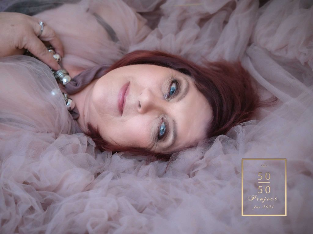 mature woman on bed in pink dress having a boudoir shoot