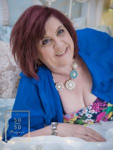 mature woman wearing a blue shirt lying on a bed for boudoir photograph for the 50 over 50 project