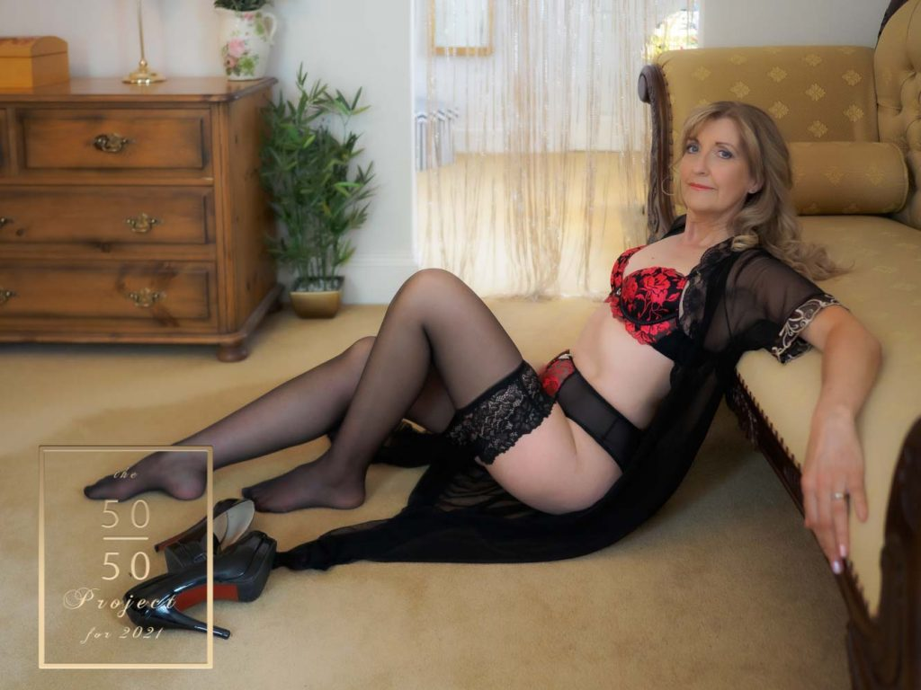 mature woman lying on a couch for boudoir photograph