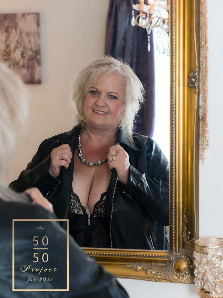 woman wearing leather jacket looking in mirror for the 50 over 50 project