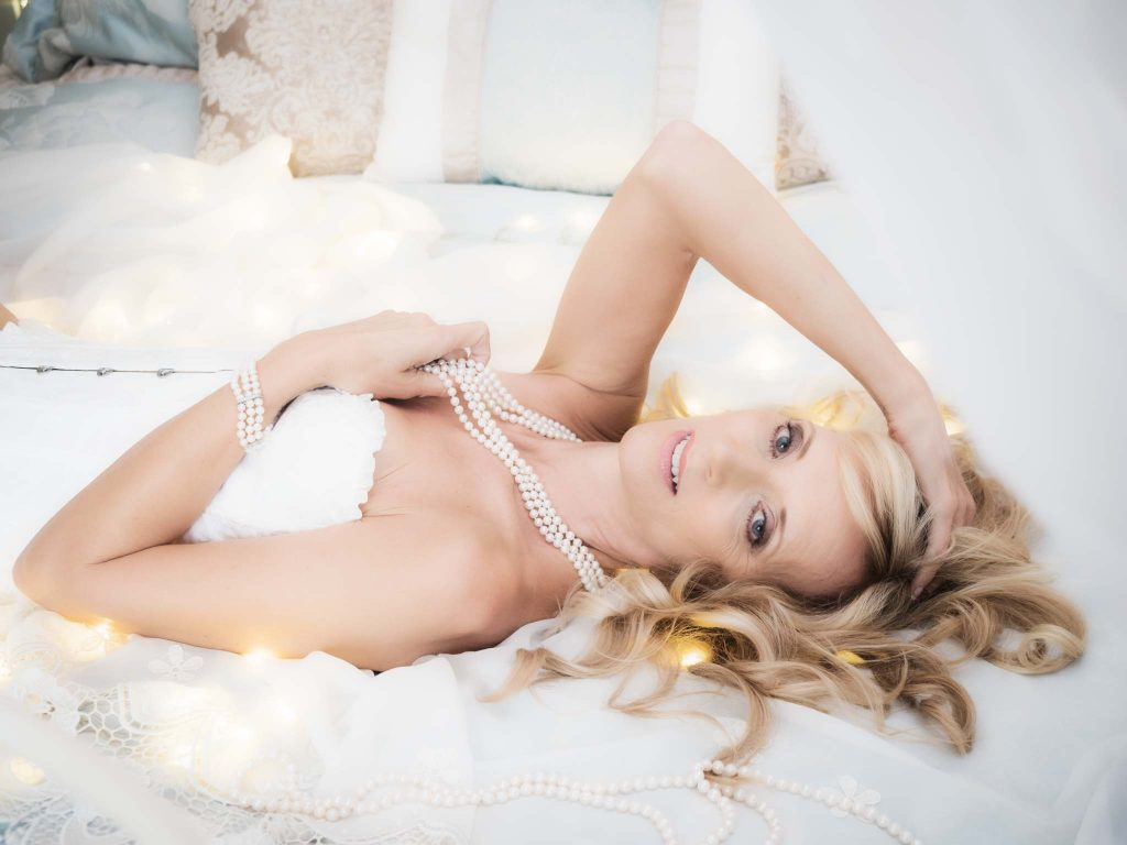 mature woman lying on bed for boudoir photograph as part of the 50 over 50 project
